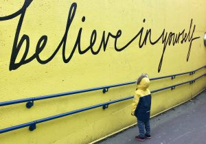 child looking at a quote - believe in yourself
