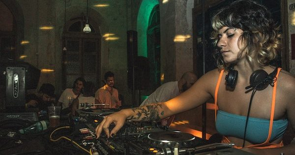 DJ woman playing music at a bar
